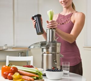 Attractive woman with juicer machine, adding celery and smiling. Horizontal.